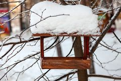 Close-up of a wooden birdhouse bird feeder covered with a large layer of snow on a clear winter day in a forest suspended from a stock photo