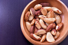 Close-up on a wooden bowl with Brazil nuts. On black background Royalty Free Stock Photography