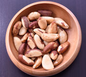 Close-up on a wooden bowl with Brazil nuts. On black background Stock Image