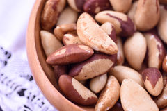 Close-up on a wooden bowl with Brazil nuts. On white background Royalty Free Stock Photo