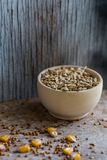 Oat grain in wooden bowl organic food concept. Close up wooden bowl filled with oat grain and different seeds scattered on table Stock Image