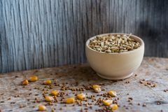 Oat grain in wooden bowl organic food concept. Close up wooden bowl filled with oat grain and different seeds scattered on table Royalty Free Stock Photography