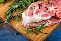 Close up wooden chopping board with raw meat  with herbs. And spices on a blue  rustic table Stock Photography