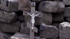 Close up for the wooden cross with crucified Jesus on stone bricks background, Bible and religion concept. Footage stock video footage