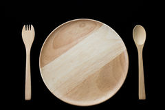 Close up wooden dish ,spoon and fork on black background Royalty Free Stock Image