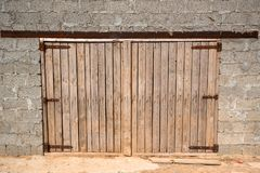 Wooden doors of brick stable on farm. Close up wooden doors of stable building on farm, view from outside Stock Images