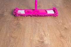 Close up of wooden floor with pink mop Stock Photos