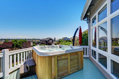 Close-up of wooden hot tub. Luxury house exterior. Blue sky background. Northwest, USA Royalty Free Stock Photos
