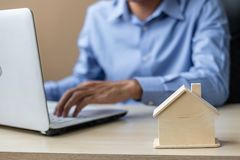 Close up wooden House model, Businessman using laptop. housing purchase, Property, real estate and insurance concepts. Close up wooden House model, Businessman royalty free stock photography