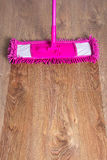 Close up of wooden parquet floor with pink mop - before after Stock Image