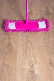 Close up of wooden parquet floor with pink mop Stock Image