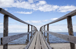 Close up of wooden pier jutting over the lake. Horizontal close up image of a wooden pier jutting over the lake into the distance  under a clear blue sky with Stock Photo