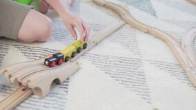 Close-up wooden rail and wagons game railroad and children`s hands.