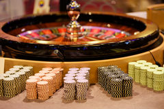 Close up of wooden roulette and chips in casino, selective focus. Close up of wooden roulette and chips in casino Royalty Free Stock Photo