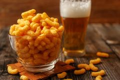 Crispy peanut puffs or flips snacks and cup of beer royalty free stock images