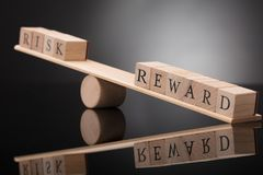 Seesaw Showing Imbalance Between Risk And Reward. Close-up Of A Wooden Seesaw Showing Imbalance Between Risk And Reward On Grey Background stock photo