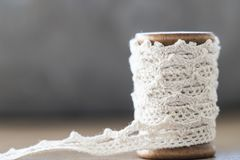 Close up wooden spool with white lace.  space for text stock photos