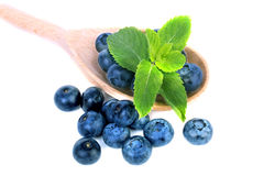 Close-up of a wooden spoon with healthful blueberries and leaves of mint, isolated on a white background. Copy space. Close-up of a pile of sweet blueberries stock image