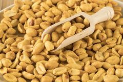 Close up wooden spoon in heap peanuts stock photography