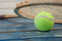 Close up of wooden tennis racket leaning on fluorescent yellow ball Royalty Free Stock Image