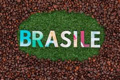 Close up of word Brasile on grass with coffee beans around stock image