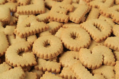 Close-up of the word GOOD spelled with alphabet shaped biscuits on the pile of same biscuits Stock Photos