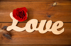 Close up of word love cutout with red rose on wood Stock Photos