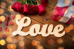 Close up of word love, red roses and gift box Royalty Free Stock Images
