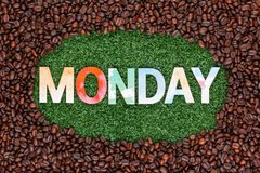 Close up of word monday on grass with coffee beans around royalty free stock photography