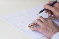 Architect draws map of house with pen, ruler and paper royalty free stock images