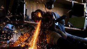 Close-up of worker cutting metal with grinder. Frame. Sparks while grinding iron. Circular cutting disc cuts of metal stock footage
