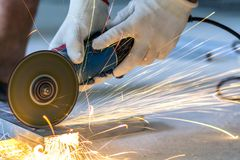 Close-up of worker cutting metal with grinder. Sparks while grin. Ding iron stock image