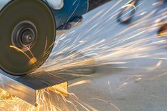 Close-up of worker cutting metal with grinder. Sparks while grin. Ding iron royalty free stock images