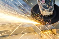 Close-up of worker cutting metal with grinder. Sparks while grin. Ding iron stock photography