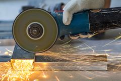 Close-up of worker cutting metal with grinder. Sparks while grin. Ding iron stock images
