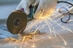 Close-up of worker cutting metal with grinder. Sparks while grin. Ding iron stock photos