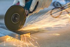 Close-up of worker cutting metal with grinder. Sparks while grin. Ding iron stock photo