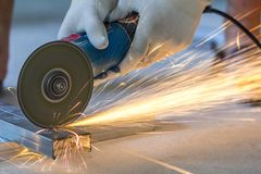 Close-up of worker cutting metal with grinder. Sparks while grin. Ding iron royalty free stock image