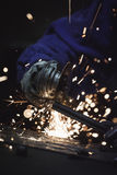 Close-up of worker cutting metal with grinder. Sparks while grinding iron. Low depth of field. Vertical photo Royalty Free Stock Image
