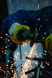 Close-up of worker cutting metal with grinder. Sparks while grinding iron. Stock Photos