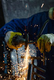 Close-up of worker cutting metal with grinder. Sparks while grinding iron. Royalty Free Stock Photo
