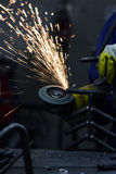 Close-up of worker cutting metal with grinder. Sparks while grinding iron. Royalty Free Stock Image