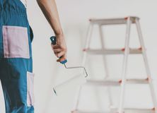 Close up. Worker Going to Paint with Paint Roller. Close up. Worker Going to Paint Wall with Paint Roller. Repair in Apartment. Modern Construction and Royalty Free Stock Images