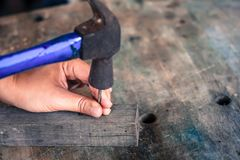 Close up worker hammering nail into wood, vintage style.  Royalty Free Stock Photography
