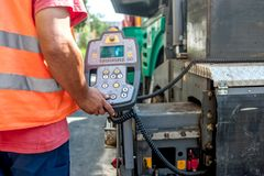 Close up of worker hand operating asphalt paver machinery Royalty Free Stock Images