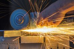 Close-up of worker hands cutting metal with grinder. Sparks whil. E grinding iron. Low depth of focus Stock Photo