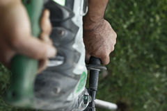 Close up of worker hands with hammer drill. Selective focus. Stock Image