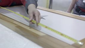 Close-up of worker measures wooden frame. Action. Control measurement of wooden frame. Worker of furniture factory. Checks dimensions of wooden frame with stock video footage