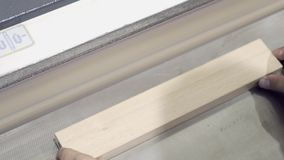 Close-up of worker processes wooden boards on grinding machine. Action. Industrial grinding machine at woodworking or. Furniture factory stock footage