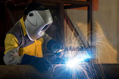 Close up of worker with protective mask welding metal Stock Photo